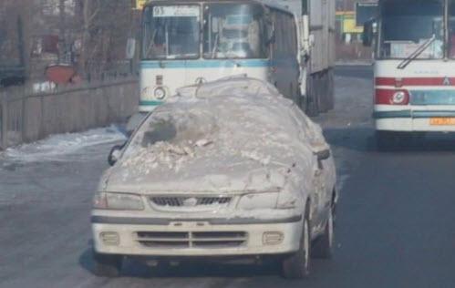 машина под снегом едет по дороге
