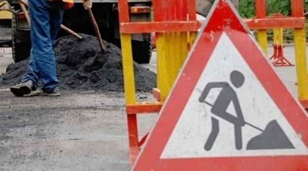рабочие укладывают асфальт на дороге
