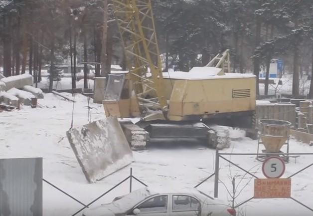 Крановщик чистит снег огромной плитой