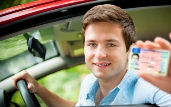 мужчина с правами за рулем